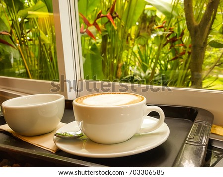Hot coffee cup on table with windows and beautiful flowers outside