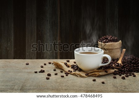 Hot Coffee cup with Coffee beans on the wooden table and the wooden wall