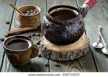 Hot coffee in clay crockery on a wooden table. Vintage style, selective focus - stock photo