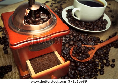 Hot Coffee in cup and coffee grinder on a wooden table - stock photo