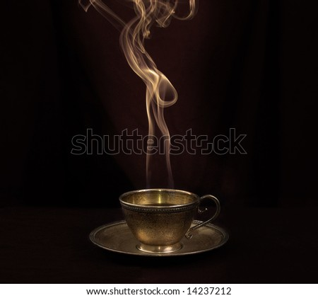 Hot coffee in gold antique cup, and smoke above - stock photo