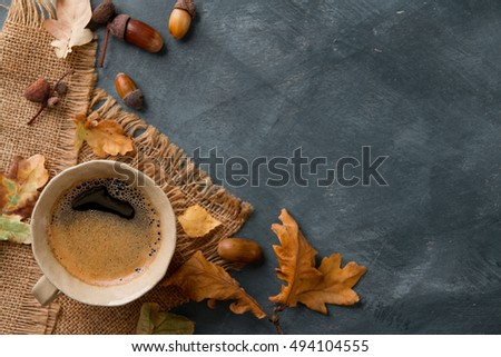 Hot coffee in mug and autumn leaf on a vintage table surface, selective focus