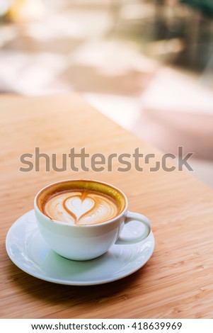 hot coffee in mug with coffee shop blur background,vintage tone - stock photo
