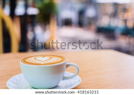 hot coffee in mug with coffee shop broke background  - stock photo