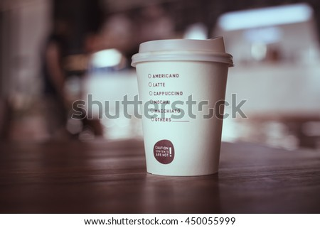 Hot coffee in paper cup with check list of coffee type  place on table - stock photo