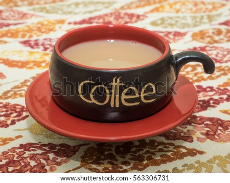 Hot Coffee In Red And Black Cup On The Table With Fall Themed Tablecloth.