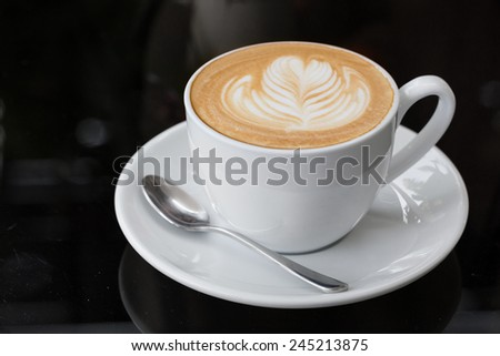 hot coffee latte, latte art with heart in white cup on a table