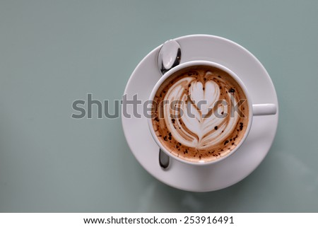hot coffee latte, latte art with heart in white cup on a table - stock photo