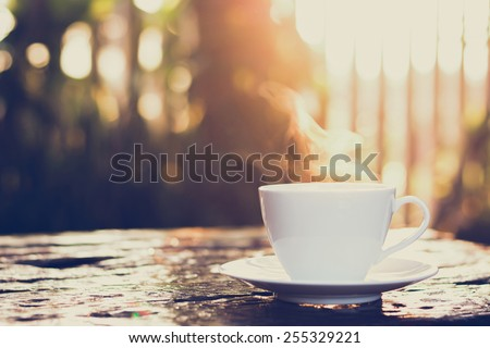 Hot coffee on old wood table with blur background of sunlight shining through the trees - soft focus, vintage style color effect - stock photo