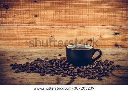 Hot coffee on pile of coffee beans with wooden background, vintage style - stock photo