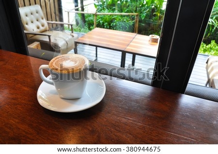 Hot coffee on the table with coffee shop background