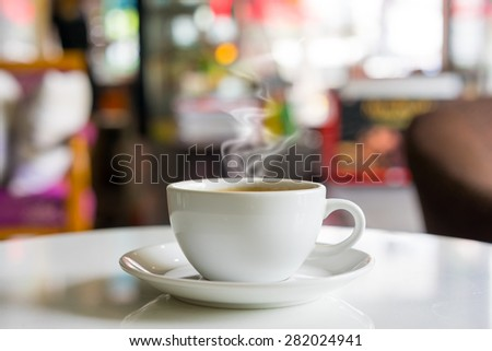 Hot coffee on white table in coffee shop background. - stock photo