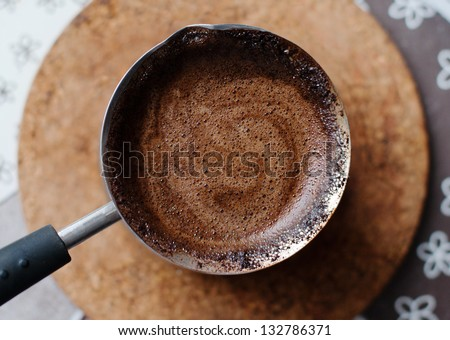 Hot coffee prepared in a Turk. Top view on a beautiful curled foam. - stock photo