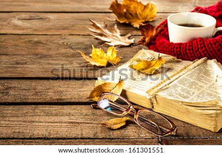 Hot coffee, vintage book, glasses and autumn leaves on wood background - relax or retirement concept with free text space - stock photo