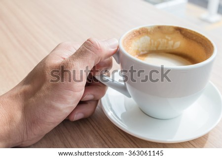 Hot coffee white cup on wood table in hand - stock photo