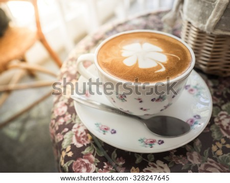 Hot coffee with a flower shaped latte art. Vintage Style - stock photo