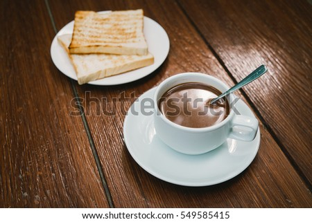 Hot coffee with bread on table background.