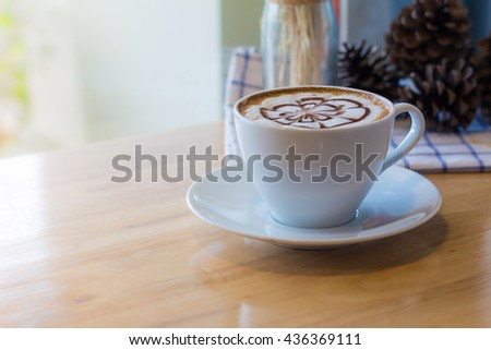 hot coffee with foam milk art in afternoon break. Hot coffee mocha on the wood desk. (selective focus, vintage effect) - stock photo