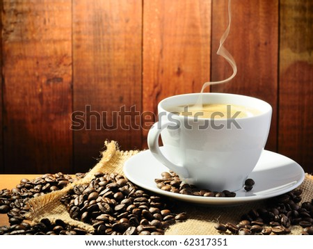 hot coffee with smoke on the grange background - stock photo