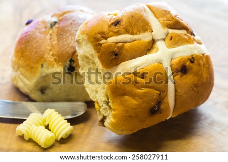 Hot cross bun made from rich yeast dough of flour, milk, sugar, butter, eggs, currants & spices. Usually eaten Good Friday, they are marked on top with a cross - stock photo
