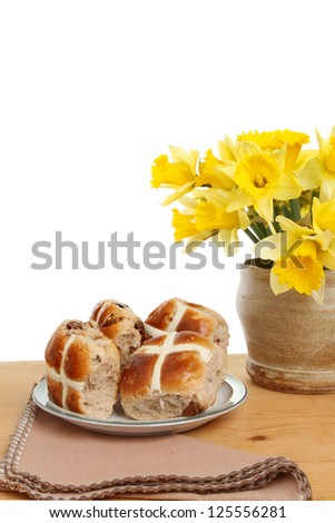 Hot cross buns and daffodils on a table against a white background - stock photo