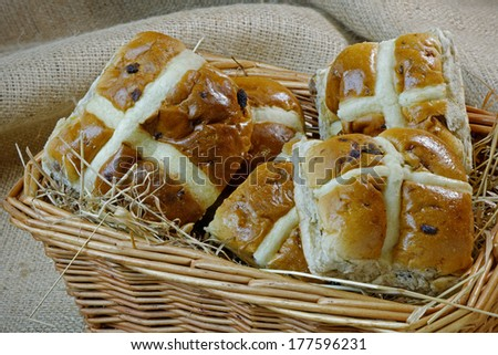Hot Cross buns lying on some hay in a basket - stock photo