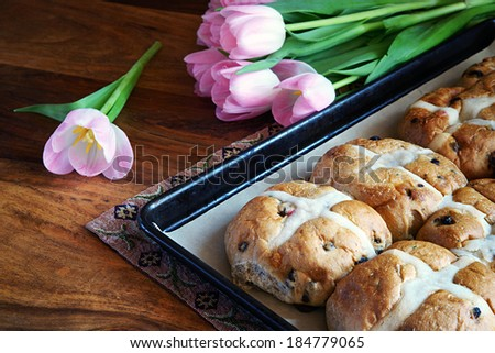 Hot cross buns on a baking pan with fresh cut tulips in the background.    - stock photo