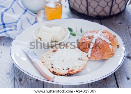 Hot cross buns on a ceramic white plate with butter and butter knife, honey and milk - stock photo