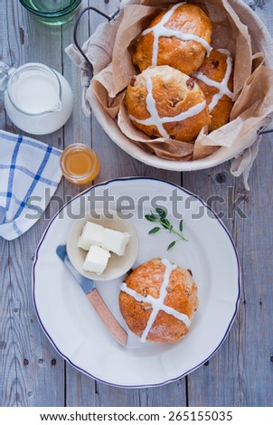 Hot cross buns on a ceramic white plate with butter and butter knife, honey and milk with basket of hot cross buns - stock photo