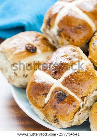 Hot cross buns, Spiced sweet bread coated in honey piled on a blue plate - stock photo