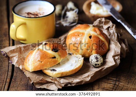 Hot cross buns with butter for Easter with quail eggs and cappuccino on rustic wooden background - stock photo