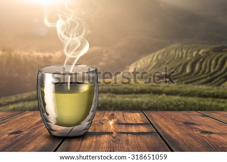 Hot Cup of Tea On Wood Table With Beautiful Sunrise Scene in Background - stock photo
