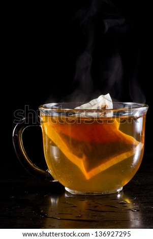 hot cup of tea served on a dark setting with steam and an anise star floating with the tea bag - stock photo