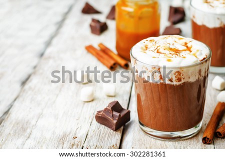 hot dark chocolate with whipped cream, cinnamon and salted caramel. the toning. selective focus - stock photo