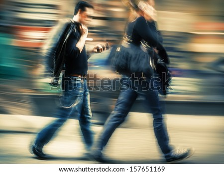 Hot day in the city. Man and woman talking on a cell phone in a hurry. Intentional motion blur and color shift - stock photo