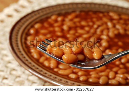 Hot delicious baked beans on fork with bowl of beans in soft focus in background.  Macro with extremely shallow dof.