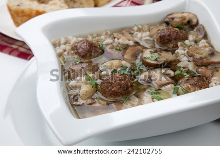 Hot delicious Mushroom Barley Soup with Mini Meatballs and cheese bread.  - stock photo