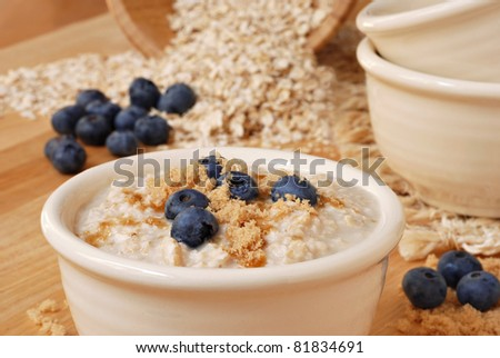 Hot delicious oatmeal and fresh blueberries sprinkled with brown sugar.  Uncooked oats in soft focus in background.  Macro with extremely shallow dof. - stock photo