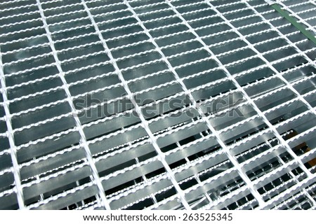 Hot-dip galvanized steel grating bunch on the rack in warehouse before shipment - stock photo