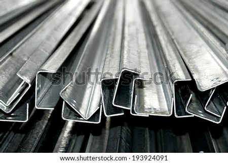 Hot-dip steel galvanized channel bunch on the rack in warehouse - stock photo