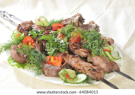 Hot dish of pieces of lamb on skewers in a dish served with vegetables. - stock photo