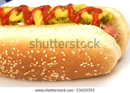 hot dog against white background with onions, pickles,ketchup and mustard on top - stock photo