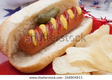 Hot dog, chips, and pickled cucumbers. Angel food fruit cakes and muffins on 4th of July in patriotic theme in background.  - stock photo