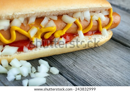 Hot dog closeup with yellow mustard , ketchup and onion on wooden surface - stock photo