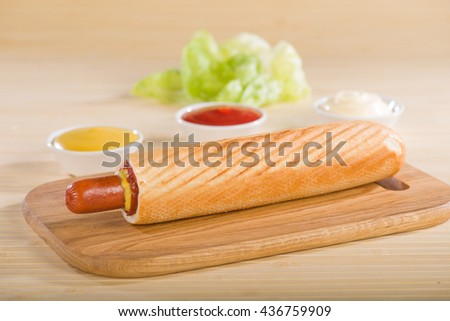 Hot Dog on a cutting board on a background of cups with ketchup and mustard. Light roll.