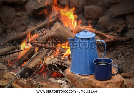 hot dog on a long fork over a fire next to an enamel coffee percolator and mug full of coffee - stock photo