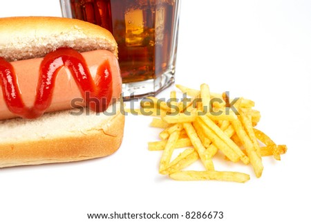 Hot dog, soda glass and french fries on white background. Shallow DOF - stock photo