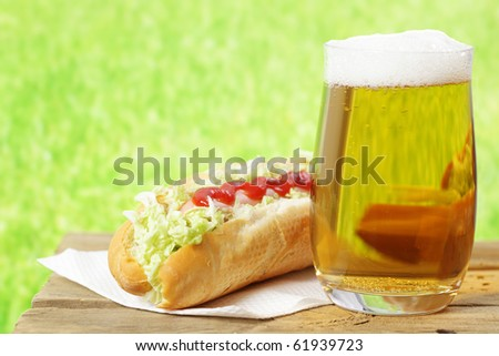 Hot dog with catchup and a glass of beer - stock photo