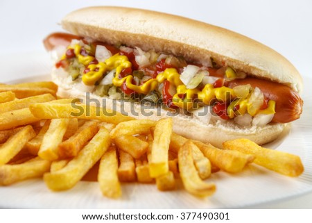 Hot dog with french fries closeup on white plate  - stock photo