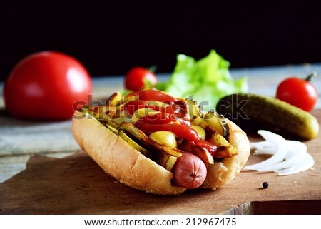 Hot dog with juicy sausage, fried potatoes, pickles, spicy mustard and sweet ketchup sauce on wooden chopping board. Low key, fast food image - stock photo